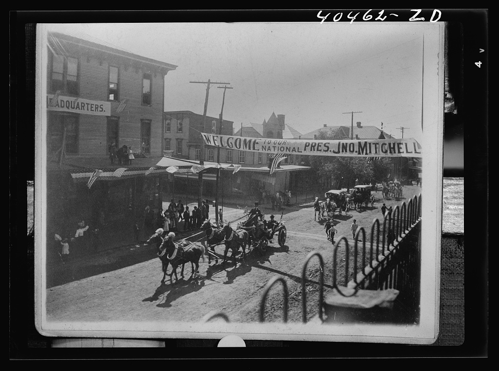 """Shenandoah, Pennsylvania. A scene in the coal mining town on the occasion of a visit by John Mitchell, labor leader. He is shown riding in a four-horse carriage, the driver of which is wearing a derby hat. Two-horse carriages follow. Above the street is a banner reading """"Welcome to our National Pres. Jno. Mitchell"""""""