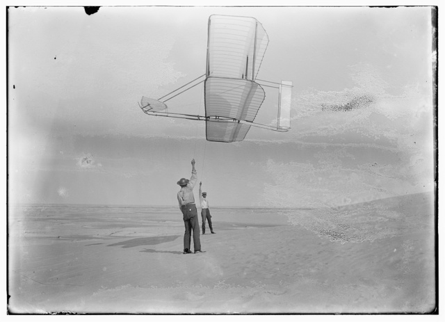 [Side view of Dan Tate, left, and Wilbur, right, flying the 1902 glider as a kite]