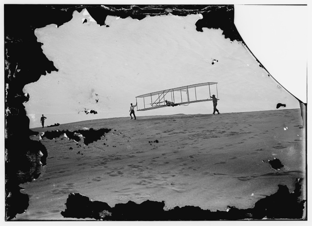 [Start of a glide; Wilbur in motion at left holding one end of glider (rebuilt with single vertical rudder), Orville lying prone in machine, and Dan Tate at right; Kitty Hawk, North Carolina]