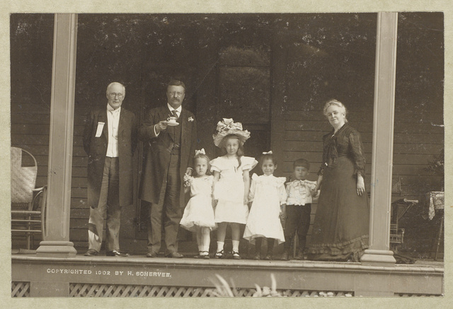 [Theodore Roosevelt, full-length portrait, standing on porch, facing front, holding cup and saucer, with older man, older woman, and four children]