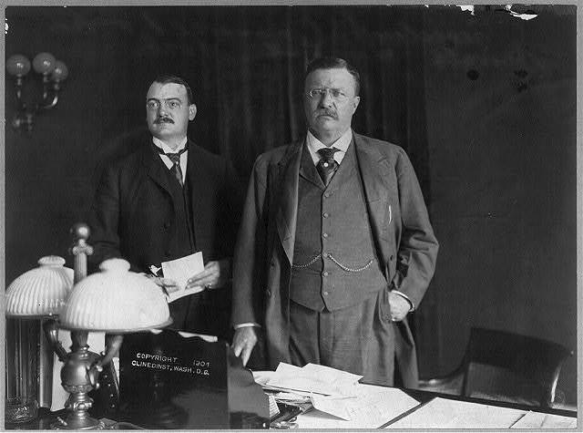 [Theodore Roosevelt standing behind desk, facing slightly left, with Presidential Secretary William Loeb]
