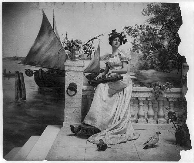 [Young woman modeling: Full lgth., leaves on head, seated on sea-wall holding zither]