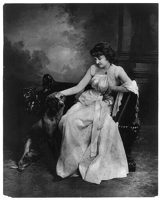 [Young woman modeling: Full lgth., seated with dog]