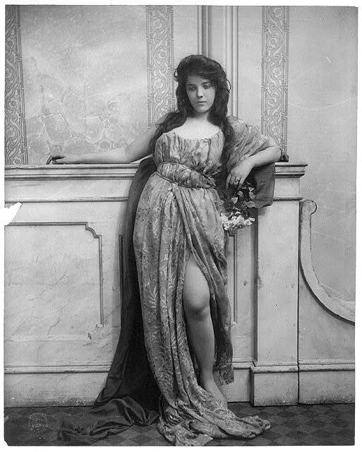 [Young woman modeling: full lgth., standing, leaning on mantle and waring split skirt]