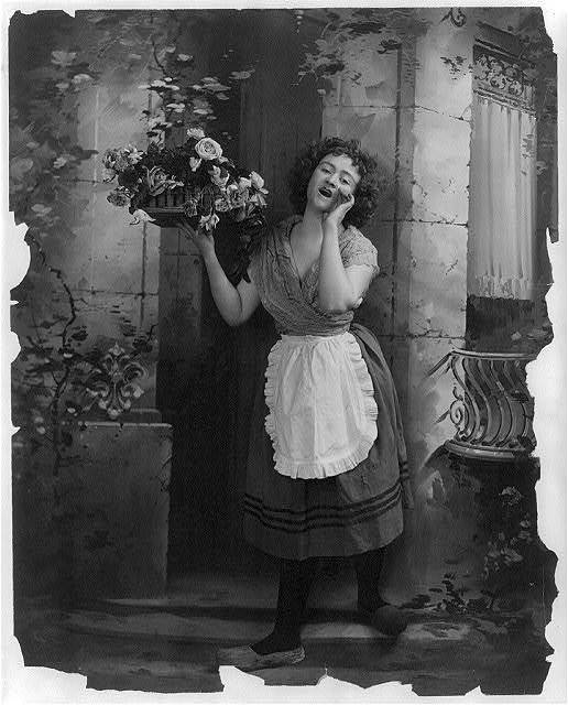 [Young woman modeling: Full lgth., standing, wearing Dutch costume and hawking tray of flowers]
