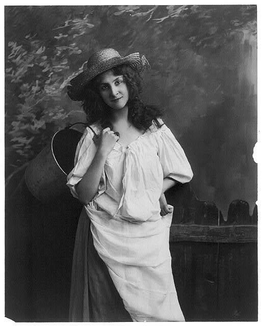 [Young women modeling: 3/4 lgth., standing, holding bucket wearing broken straw hat]