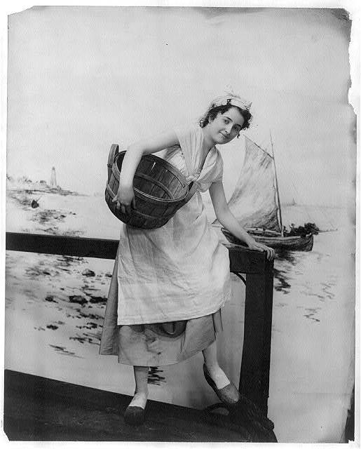 [Young women modeling: Full lgth., wearing Dutch costume, holding basket, and standing on pier]
