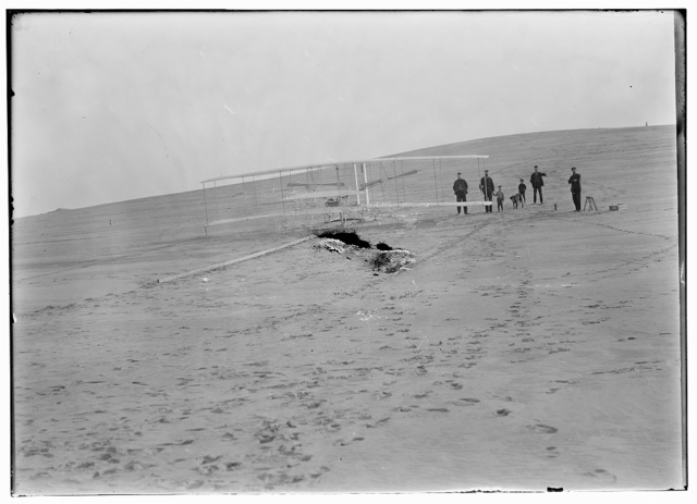 [1903 machine on the launching track at Big Kill Devil Hill, prior to the December 14th trial. Four men from the Kill Devil Hills Lifesaving Station helped move it from the shed to the hill, accompanied by two small boys and a dog]