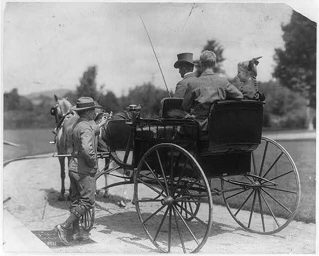 [3 people in horse-drawn carriage and another man getting on the carriage]