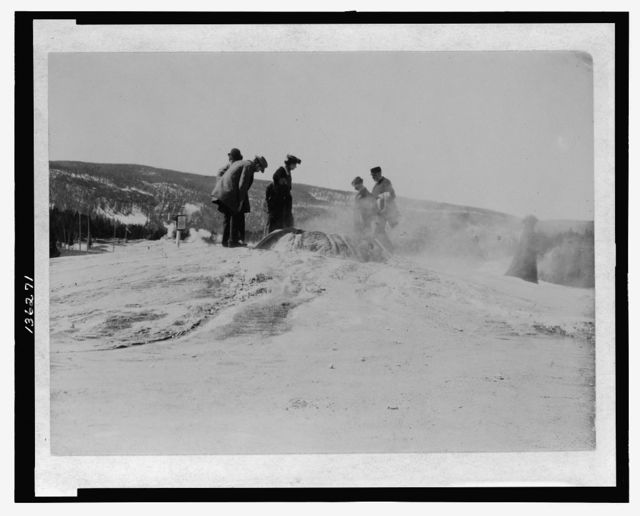 [A group of tourists explore a geyser in the Upper Geyser Basin in Yellowstone National Park]