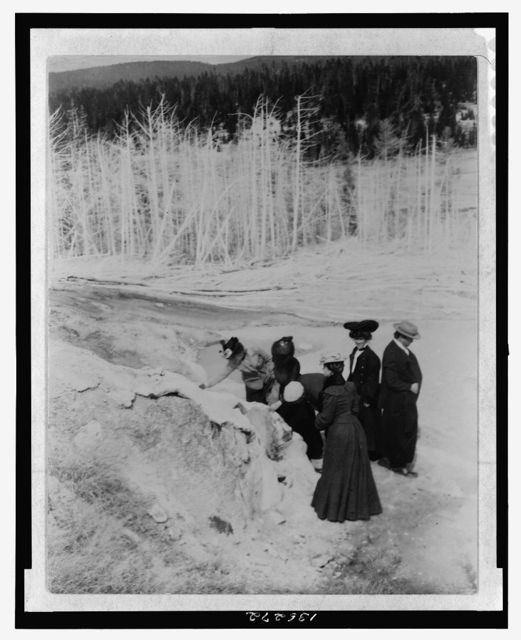[A group of tourists explore land formations in Yellowstone National Park]