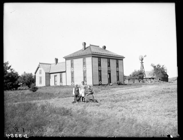 Couple in front of George Fleahearty's two-story frame farmhouse near Buda, Buffalo County, Nebraska.