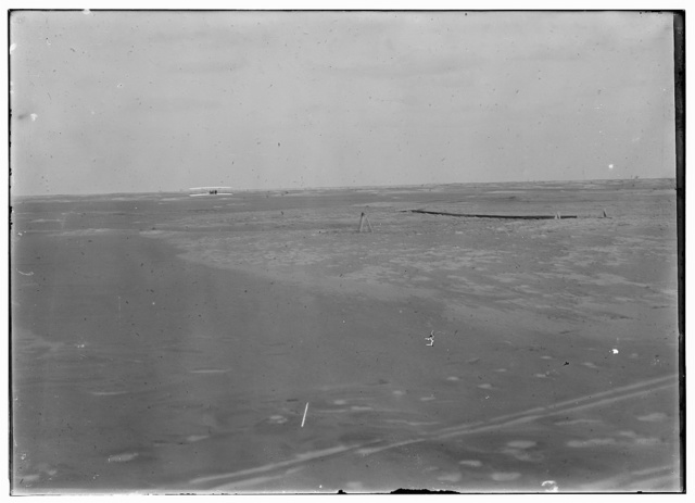 [Distant view of the Wright airplane just after landing, taken from the starting point, with wing-rest in center of picture and launching rail at right. This flight, the fourth and final of December 17, 1903, was the longest: 852 feet covered in 59 seconds.]