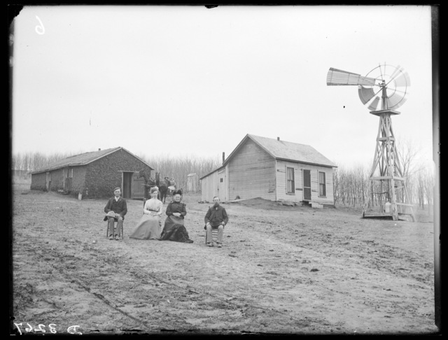 Family in front of a sod house with a frame house to right on the L.W. Hall farm, Miller, Nebraska.