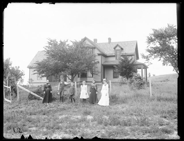 Family in front of A.A. Whitney's farmhouse at Riverdale, Buffalo County, Nebraska.