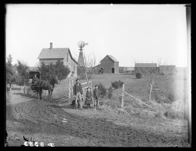 Family in front of C.E. Brigham's two-story frame farmhouse in Buffalo County, Nebraska.