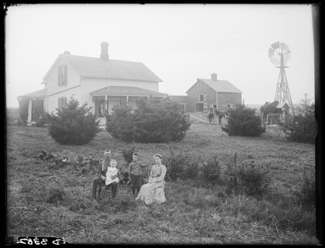 Family in front of two-story frame farmhouse in Buffalo County, Nebraska.
