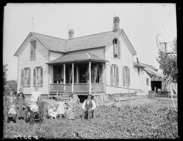 Family seated in front of two-story frame farmhouse, Buffalo County, Nebraska.