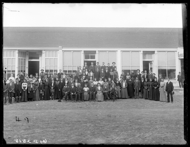 Group photo of students and staff outside in front of the Broken Bow College.