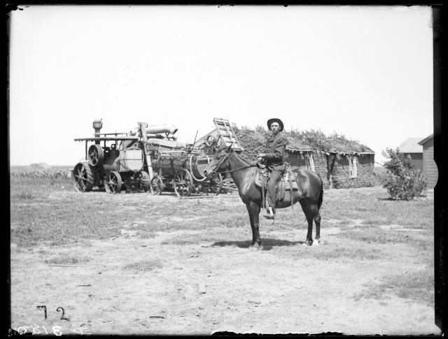 H. Stover on horse with sod house and threshing machine in background, Riverdale, Nebraska.