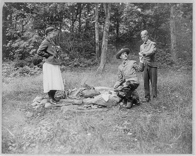 [Henry Van Dyke and 2 others with sandwiches at campfire]