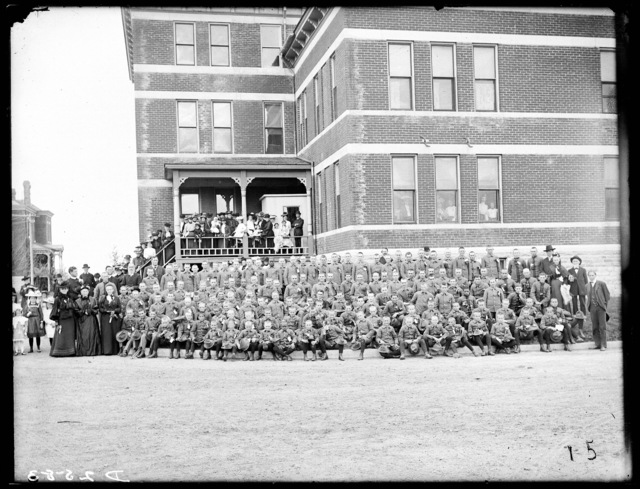 Large group of peoplealong with Industrial School students outside the school building at Kearney, Nebraska.