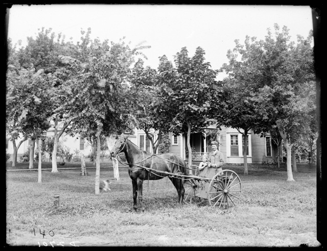 Man and small girl on horse drawn cart in front of A.C. Everson house Kearney, Nebraska.