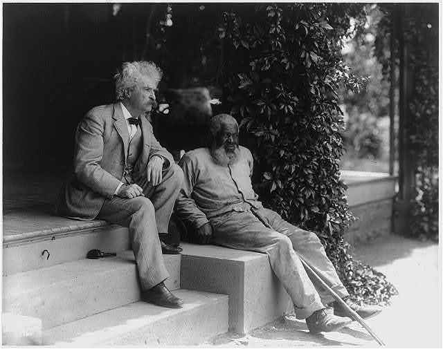 Samuel Clemens and John T. Lewis (an elderly African American man), both full length, seated on steps of porch