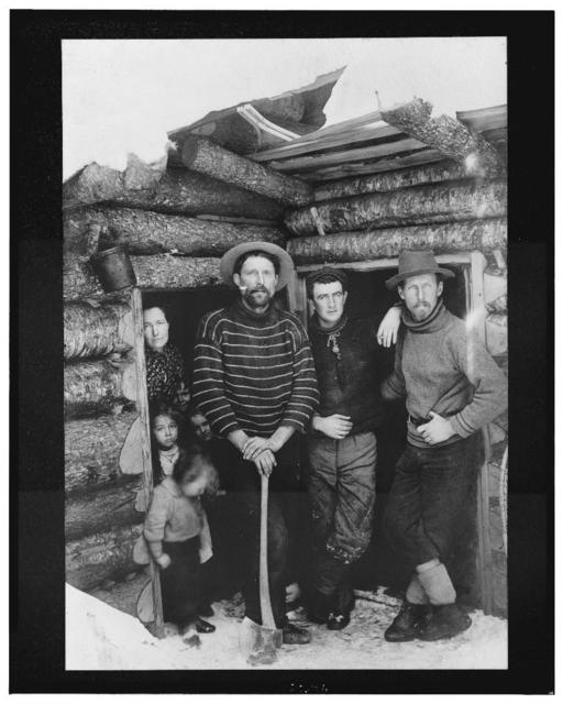 [Three men, one of them holding an axe, a woman, and four children standing at two doorways of a log cabin]