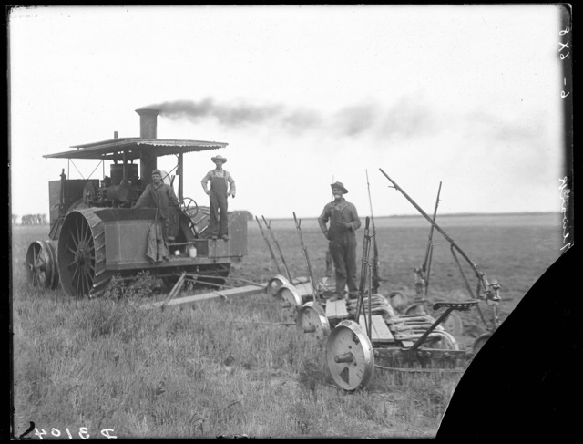 Three men standing with a  steam tractor pulling a plow.  The machine is owned by Radford and sons, at Newark, Buffalo County, Nebraska