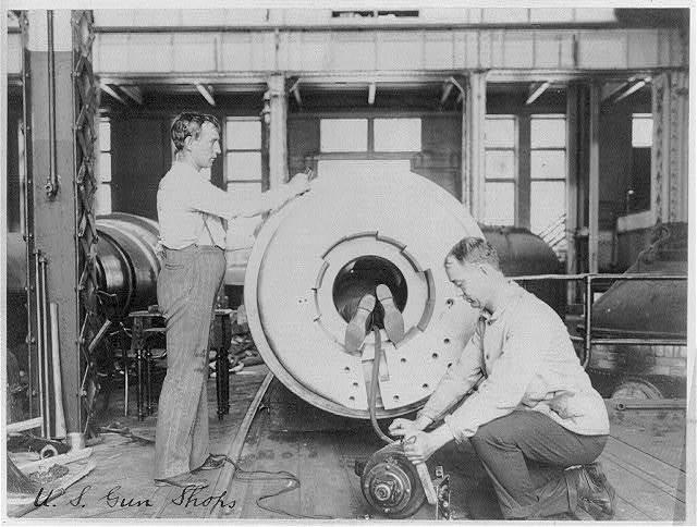 [Three men working on large gun in Naval Gun Factory, Washington, D.C.; one of the men lying in the barrel]