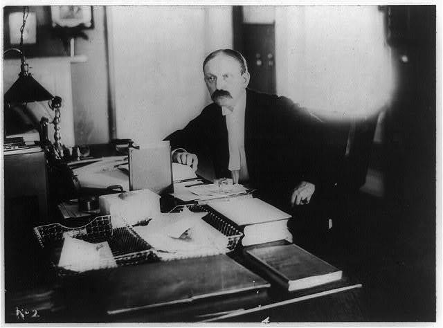 [William Woodville Rockhill, American diplomat, head-and-shoulders portrait, facing left, seated at desk]