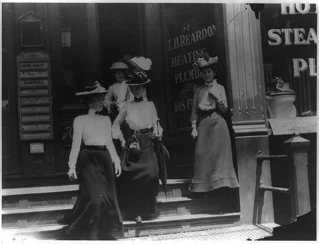 [Women coming from work, Cal.?. Store window reads T.B. Reardon, heating and plumbing]