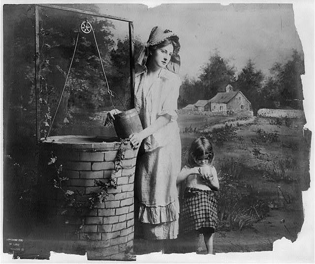 [Young woman modeling: Full lgth., standing at well, with little girl]