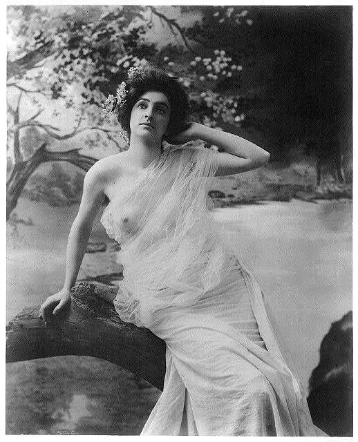 [Young woman modeling: Nude seated on log]