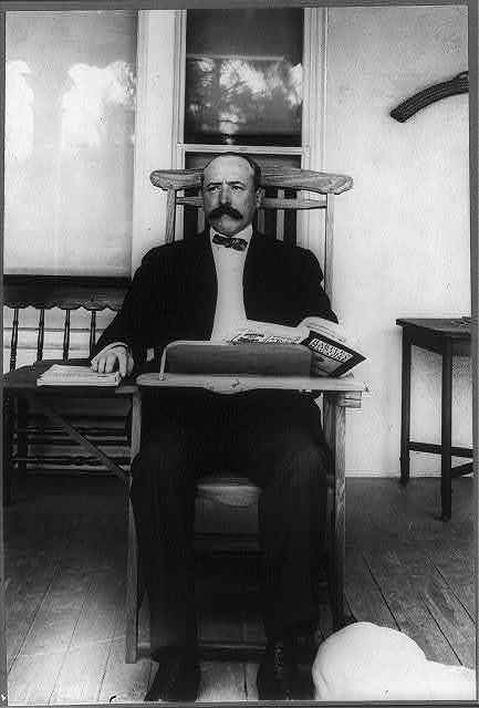 [Alton Brooks Parker, 1852-1926, full length portrait, seated, facing slightly left; in classroom desk chair reading Harper's Magazine]