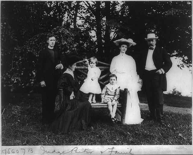 [Alton Brooks Parker, 1852-1926, full length, standing, facing slightly left; with family, incl. wife, son-in-law in clerical robe; step-daughter, and 2 grandchildren, on lawn]