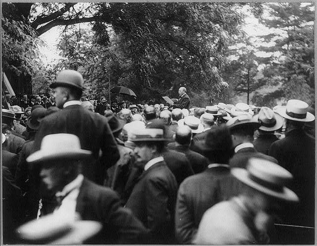[Alton Brooks Parker, 1852-1926, half length, standing, facing left; making speech to large group of men]