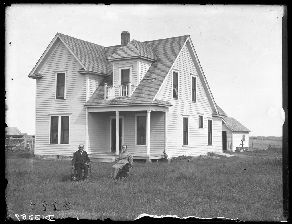 Couple seated in front of the Crispen farmhouse, Buffalo County, Nebraska.