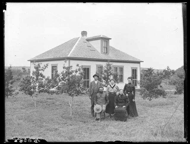 Family in front of one-story frame house in Buffalo County, Nebraska.