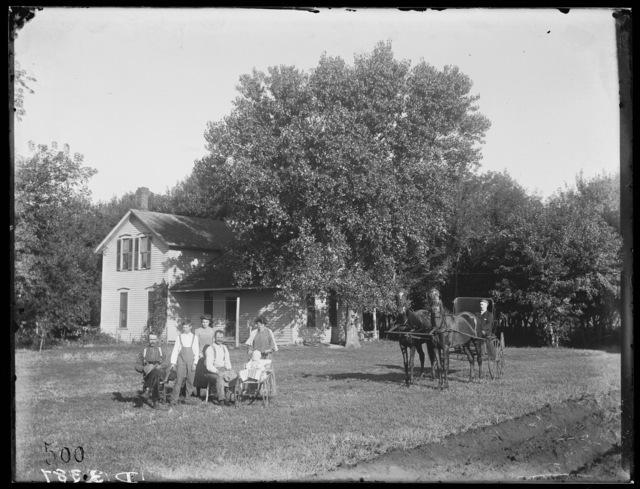 Family in front of two-story frame house in Waldron, Buffalo County, Nebraska.