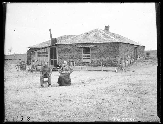 James Wood, an old timer, and wife in front of their old sod house, Dale Valley, Nebraska.