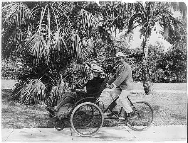 Joe Jefferson [on seat on front of quadricycle being peddled by another man], Palm Beach, Fla.