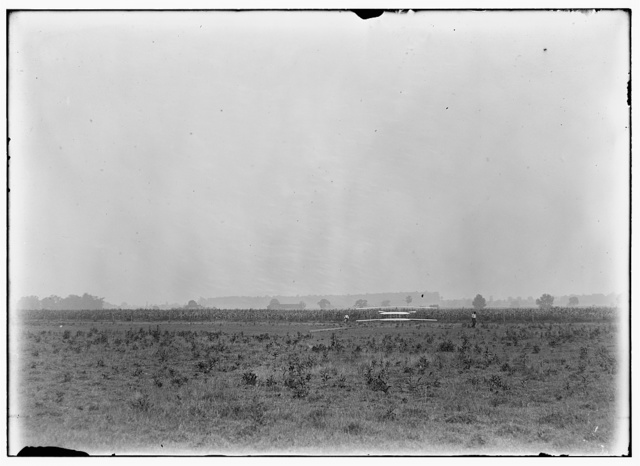 [Long-range view of machine on launching track, probably Wilbur and Orville standing on either side; Huffman Prairie, Dayton, Ohio]