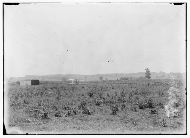 [Long-range view of machine on launching track, showing hangar nearby and hummocky ground of former swamp at Huffman Prairie, Dayton, Ohio]