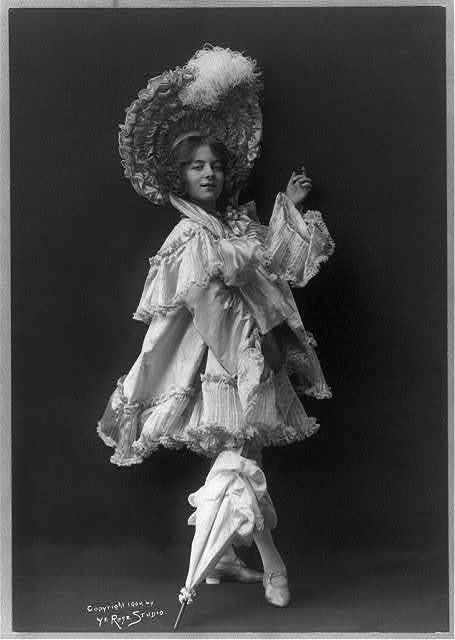 [Model posed in ornate costumes: in white, ruffled satin with large plumed hat and parasol]