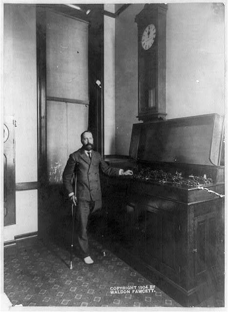 [One-legged man on crutches and instrument, with clock above reading 12:00, at the United States Naval Observatory, 3450 Massachusetts Ave., N.W., Washington, D.C.] / copyrighted and photographed by Waldon Fawcett.