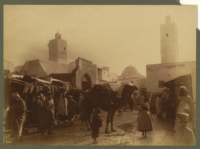 One of the main streets of Kairouan, showing two of the minarets. The archway over the camel is the entrance to the souks or bazaars / Lehnert et Landrock, Tunis.