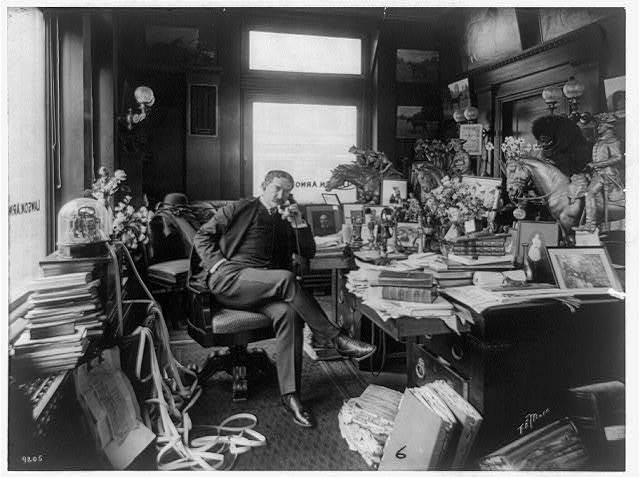 [Thomas W. Lawson, full-length portrait, seated at desk, facing right, on telephone, alongside ticker tape machine]