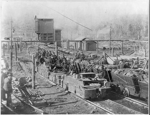 [Train-load of ore and miners outside Davis Coal and Coke Industry]